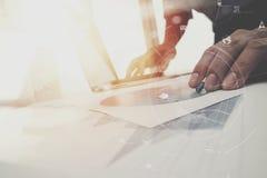 Geschäftsmann, der mit Handy und digitale Tablette und Schoss arbeitet Stockbild