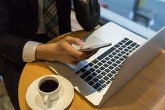 Geschäftsmann, der mit intelligentem Telefon und Laptop auf hölzernem rundem Schreibtisch als Konzeptkaffee arbeitet Lizenzfreie Stockfotos