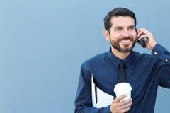 Geschäftsmann, der mit Kaffee und Ordner mit Dokumenten am Telefon geht Lizenzfreie Stockfotografie