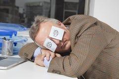 Geschäftsmann, der mit klebrigen Anmerkungen über Augen am Schreibtisch im Büro schläft lizenzfreie stockbilder