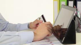 Geschäftsmann, der mit Kreditkarte durch Tablette zahlt stock footage