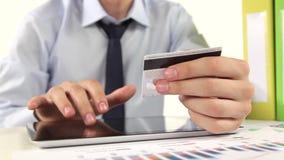 Geschäftsmann, der mit Kreditkarte durch Tablette zahlt stock video footage