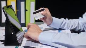 Geschäftsmann, der mit Kreditkarte durch Tablette, an zahlt stock video