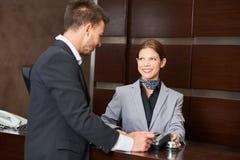 Geschäftsmann, der mit Kreditkarte im Hotel zahlt lizenzfreie stockfotos