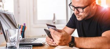 Geschäftsmann, der mit Kreditkarte am intelligenten Telefon zahlt Stockfoto