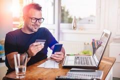 Geschäftsmann, der mit Kreditkarte am intelligenten Telefon zahlt Stockfotos