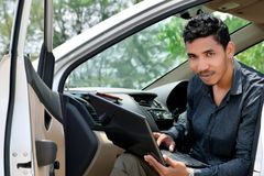 Geschäftsmann, der mit Laptop arbeitet und im Auto sitzt stockfotos