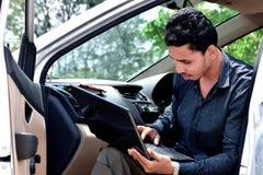 Geschäftsmann, der mit Laptop arbeitet und im Auto sitzt stockfoto