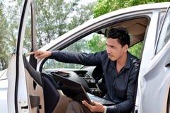 Geschäftsmann, der mit Laptop arbeitet und im Auto sitzt lizenzfreie stockfotos