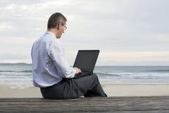 Geschäftsmann, der mit Laptop auf einem Strand arbeitet Stockfotos