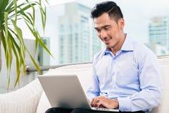 Geschäftsmann, der mit Laptop vom Haus arbeitet Stockbilder