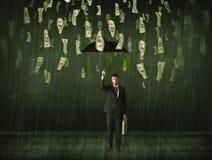 Geschäftsmann, der mit Regenschirm im Dollarschein-Regenkonzept steht Lizenzfreie Stockfotos