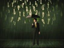 Geschäftsmann, der mit Regenschirm im Dollarschein-Regenkonzept steht Stockfotografie