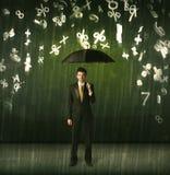 Geschäftsmann, der mit Regenschirm stehen und Zahlen 3d, die concep regnen Lizenzfreie Stockfotografie
