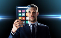 Geschäftsmann, der mit transparentem Tabletten-PC arbeitet Lizenzfreie Stockfotos
