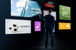 Geschäftsmann, der mit virtuellen Anwendungen arbeitet stockbild