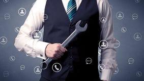 Geschäftsmann, der mit Werkzeug auf seiner Hand bleibt Stockbilder