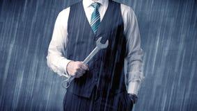 Geschäftsmann, der mit Werkzeug auf seiner Hand bleibt Lizenzfreies Stockfoto