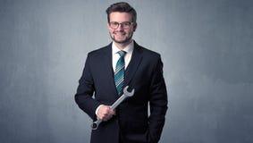 Geschäftsmann, der mit Werkzeug auf seiner Hand steht Stockbild