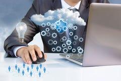 Geschäftsmann, der mit Wolkendaten bezüglich des Laptops arbeitet Lizenzfreie Stockfotografie