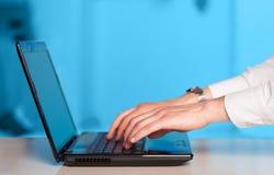 Geschäftsmann, der moderne Laptop-Computer auf buntem backgrou bedrängt Stockbilder
