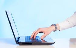 Geschäftsmann, der moderne Laptop-Computer auf buntem backgrou bedrängt Lizenzfreies Stockbild