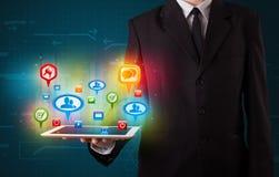 Geschäftsmann, der moderne Tablette mit bunten Sozialzeichen darstellt Stockbilder