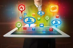 Geschäftsmann, der moderne Tablette mit bunten Sozialzeichen darstellt Stockfotografie