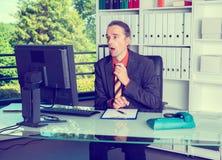 Geschäftsmann, der Monitor überrascht betrachtet Lizenzfreie Stockbilder