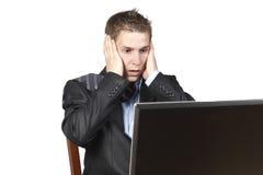 Geschäftsmann, der nahe bei einem Laptop sitzt Lizenzfreies Stockbild