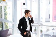 Geschäftsmann, der nahe dem Fenster steht und am Handy spricht Stockbilder