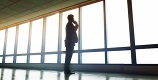 Geschäftsmann, der nahes Bürofenster steht und auf beweglichem pH spricht Lizenzfreie Stockbilder
