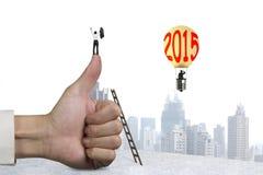 Geschäftsmann, der oben auf Daumen mit Ballon der Heißluft 2015 zujubelt Stockfotografie
