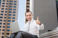 Geschäftsmann, der oben auf Schritten unter Verwendung des Laptopdaumens sitzt Stockfotografie
