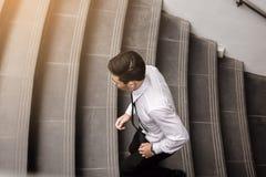 Geschäftsmann, der oben das Treppenhaus geht zu arbeiten laufen lässt stockfotografie