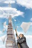 Geschäftsmann, der oben den Stapel der Schreibarbeit steigt Lizenzfreies Stockfoto
