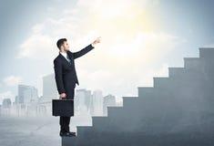 Geschäftsmann, der oben ein konkretes Treppenhauskonzept klettert Stockfotografie