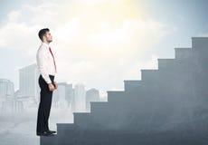 Geschäftsmann, der oben ein konkretes Treppenhauskonzept klettert Lizenzfreies Stockfoto