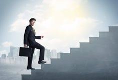 Geschäftsmann, der oben ein konkretes Treppenhauskonzept klettert Stockbild