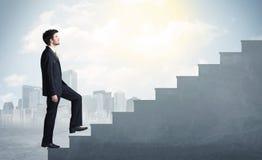 Geschäftsmann, der oben ein konkretes Treppenhauskonzept klettert Lizenzfreie Stockbilder