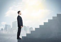 Geschäftsmann, der oben ein konkretes Treppenhauskonzept klettert Lizenzfreie Stockfotos