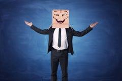 Geschäftsmann, der oben Hände anhebt und Kasten auf seinem Kopf mit dem lachenden Gesicht gemalt trägt Stockbild