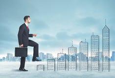 Geschäftsmann, der oben an Hand gezeichnete Gebäude in der Stadt klettert Lizenzfreie Stockfotografie