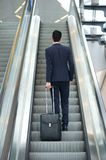 Geschäftsmann, der oben Rolltreppe mit Tasche geht Lizenzfreies Stockfoto