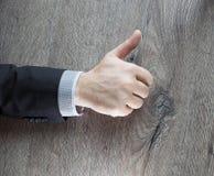 Geschäftsmann, der OKAYzeichen mit seinem Daumen oben lokalisiert mit dunklem hölzernem Hintergrund zeigt Erfolgsgeschäftsvereinb Lizenzfreie Stockfotografie