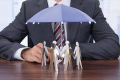Geschäftsmann, der Papierleute mit Regenschirm schützt Stockbilder