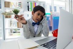 Geschäftsmann, der Papierwährung bei der Unterhaltung am Handy hält Stockbild
