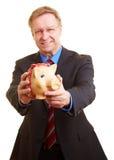 Geschäftsmann, der piggy Querneigung offerering ist lizenzfreie stockfotos