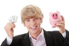 Geschäftsmann, der piggy Querneigung und Geld anhält Stockfotos