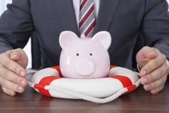 Geschäftsmann, der piggybank mit Rettungsgürtel am Schreibtisch schützt Lizenzfreies Stockbild